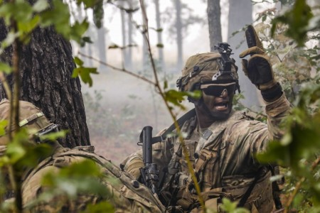 A Soldier signals his team toward the breach point during a live-fire exercise at Fort Polk, La., Oct. 27, 2020.