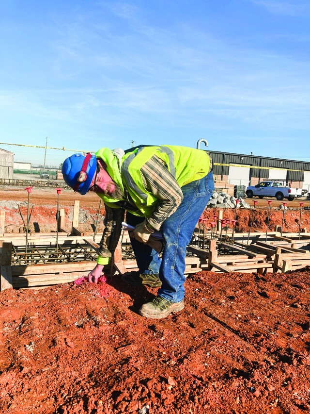 Jeff Abbott of Haase Mechanical Contractors helps lay markers Dec. 9, at the construction site of the Army Field Support Battalion Installation Maintenance Division complex on post.