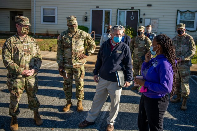 FORT BENNING, Ga. – The Maneuver Center of Excellence command team, consisting of Maj. Gen. Patrick J. Donahoe, commanding general, Command Sgt. Maj. Derrick C. Garner, command sergeant major, and Kirk Ticknor, Housing chief, discuss the neighborhood's trash pickup with Spc. Carletha Ingram, 1st Battalion, 28th Infantry Regiment, Dec. 9, 2020, at Bouton Heights. (U.S. Army photo by Patrick A. Albright, Maneuver Center of Excellence and Fort Benning Public Affairs)