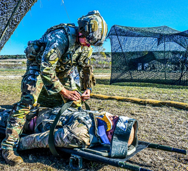 A Soldier secures a medical dummy to a litter as part of the evaluating a casualty task while participating in the Expert Infantryman Badge/Expert Soldier Badge Qualification Course, November 25, 2020, at Fort Hood, TX. The EIB/ESB Qualification is being held by 2nd Armored Brigade Combat Team, 1st Cavalry Division, Fort Hood, TX, until Dec 11. (Army photo by SGT. Broderick Hennington)
