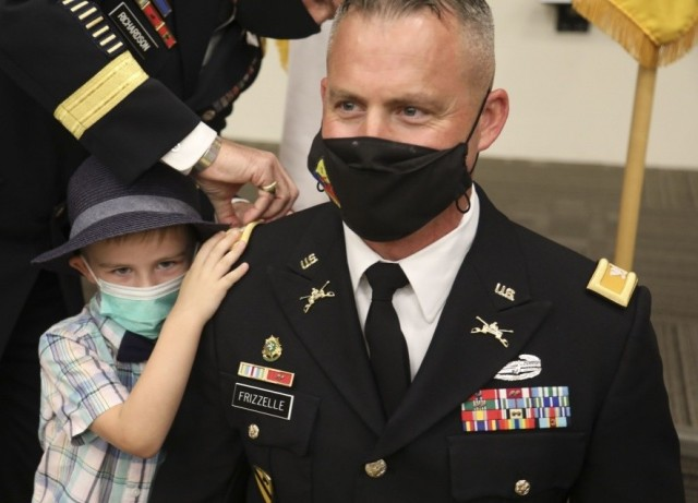 Lt. Col. Bryan W. Frizzelle's son pins a new shoulder board to his father's Army Service Uniform coat during a special promotion ceremony held at 1st Armored Division Headquarters at Fort Bliss, Texas Oct. 16, 2020.