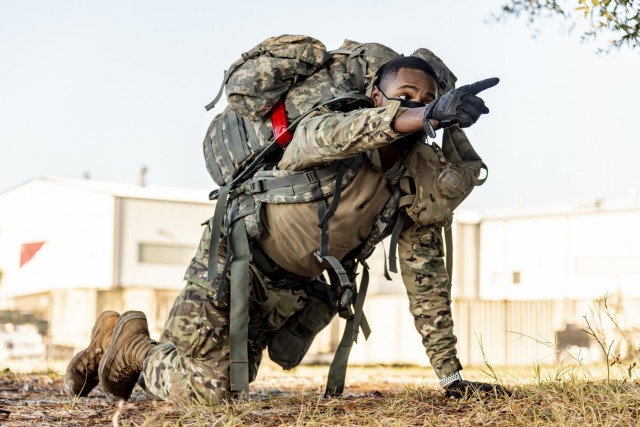 Spc. Devin Jordan, a motor transport operator assigned to Headquarters and Headquarters Company, 83rd Chemical, Biological, Radiological, and Nuclear Battalion, directs his team as cadre called enemy contact during mock Tactical Combat Casualty Care,  Dec. 10, 2020 on Fort Stewart, Georgia. The TCCC lane, part of HHC's Ghost Rider Challenge, consisted of an assessment, treatment and movement of a casualty to safety for medical evacuation. (U.S. Army photo by Spc. Robert P Wormley III)