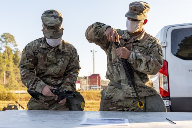 Pvt. Josue Vasallo, a wheeled vehicle mechanic, and Pfc. Willy Calle, a generator mechanic, both assigned to Headquarters and Headquarters Company, 83rd Chemical, Biological, Radiological, and Nuclear Battalion demonstrate their ability to disassemble and reassemble an M4 carbine on Fort Stewart, Georgia Dec. 10, 2020. The weapons lane, part of HHC's Ghost Rider Challenge, consisted of timed disassembly and reassembly of an M9 Pistol, M4 Carbine and an M249 Squad Automatic Weapon. (U.S. Army photo by Spc. Robert P Wormley III)