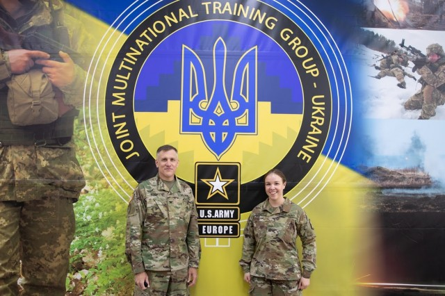 U.S. Army Col. Paul Schmitt and his daughter, Second Lieut. Schmitt, stand in front of a sign for the Joint Multinational Training Group-Ukraine. Schmitt serves as the Army Attaché to the U.S. Embassy in Kviv, Ukraine and is a participant in the pilot for the new retirement extension program aimed at retaining officers with unique talents to meet critical requirements.