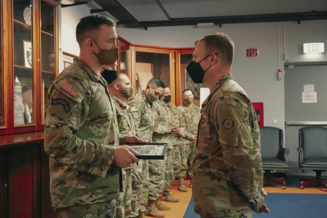 U.S. Army Command Sgt. Maj. Michael Burke (left) of the 2d Cavalry Regiment, awards a student his diploma from graduating the 2d Cavalry Regiment's Platoon Sergeant University in Vilseck, Germany, Dec. 4, 2020. The course aimed to develop leaders' character, passion and emotional intelligence. (U.S. Army photo by Sgt. LaShic Patterson)