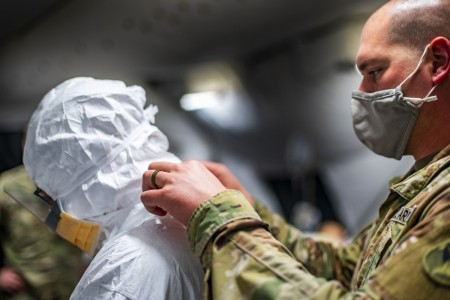 Army Maj. David Alford, a critical care nurse assigned to the 396th Combat Support Hospital, Joint Task Force Bravo, receives assistance putting on a medical protective suit during COVID-19 battle drill rehearsals at Soto Cano Air Base, Honduras, Aug. 13, 2020.