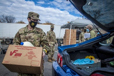 Connecticut Army National Guardsman Staff Sgt. Samantha Sheehan loads a box of groceries for a family at a drive-thru food distribution point for the Farmers to Families Program in New Haven, Conn., Oct. 27, 2020.