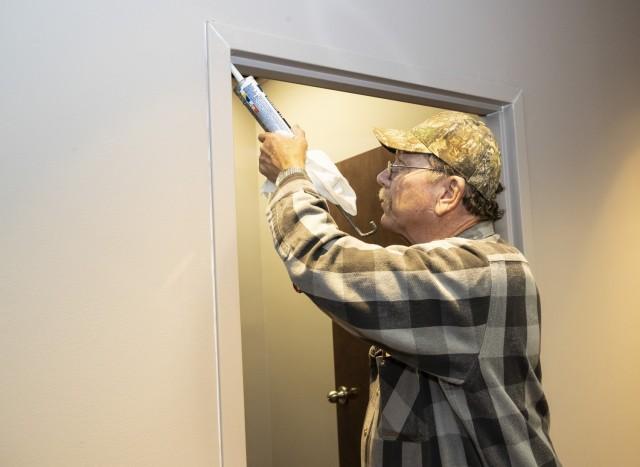 Ralph Mange, a DPW maintenance mechanic, caulks a doorframe in the Headquarters' building.