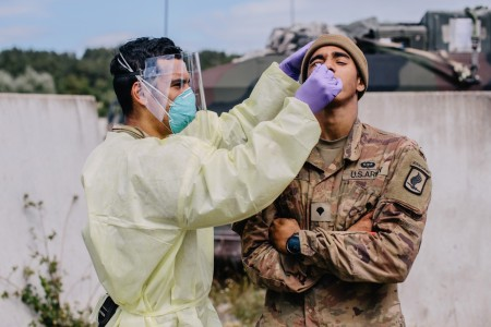 An Army medic paratrooper swabs a soldier for COVID-19 during Exercise Saber Junction at the Hohenfels Training Area, Germany, Aug. 20, 2020.
