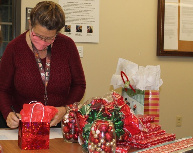 Linda Albrecht, a metallurgical engineer, checks another toy off a list of gifts USAEC volunteers prepared for delivery.
