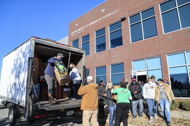 On Dec. 10, Anniston Army Depot employees assist the Department of Human Resources staff in unloading three trucks fill with Christmas gifts for children in the Family Preservation Program.