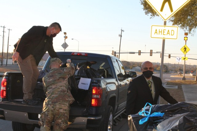 U.S. Army Environmental Command employees load gifts for delivery to the Fort Sam Houston Elementary School as part of their Angel Tree program.
