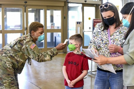 A service member conducts a temperature check during a flu vaccination event for Army family members and military retirees at Fort Bliss, Texas, Oct. 9, 2020. This year's event included the temperature checks as well as social distancing and masks due to the coronavirus pandemic.