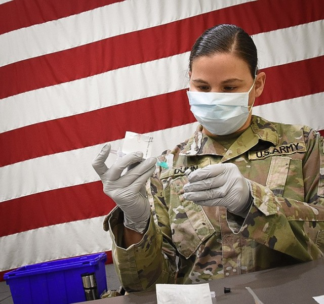 After diluting a vial's contents a COVID-19 vaccine must be gently inverted 10 times to mix. Technicians must record the time of dilution on a label to ensure vaccine is administered within six hours. (U.S. Army Photo/Tywanna Sparks)