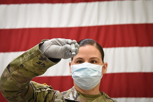 Staff Sgt. Courtney Dunn, an Irwin Army Community Hospital pharmacy technician, rehearses the process of inverting a mock thawed vaccine vial gently 10 times before dilution, according to a manufacturer's COVID-19 vaccine product. Vials are stored in an ultra-low temperature freezer, thawed, diluted and used within six hours of dilution. (U.S. Army Photo/Tywanna Sparks)
