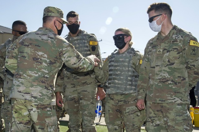 Gen. Paul Funk II, U.S. Army Training and Doctrine Commander presents the winning team of the Best Advanced Individual Training (AIT) Medic Competition a commander's coin for excellence at Joint Base San Antonio-Fort Sam Houston, Texas on December 17, 2020.  The winners (from left to right) are 68W combat medics in training: Pvt. Aneese Williams, Pvt. Aaron Freeman, Pvt. Jade Berget and Pvt. Christian York. Photo courtesy Joint Base San Antonio Multimedia.
