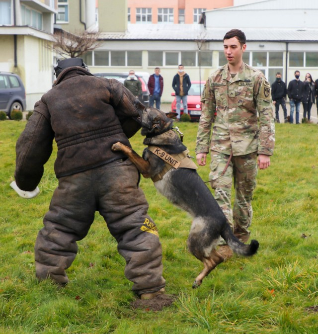 U.S. Army Cpl. Dustin Borchardt, a military dog handler with the 100th Military Police Detachment based out of Stuttgart, Germany, gives a bite suit demonstration with his military working dog in Ferizaj/Ferizaje, Kosovo, on Dec. 8, 2020. Borchardt and his dog Pearl travelled to the School of Agribusiness and Food Technology to share knowledge about working dogs and build a relationship with the local community.
