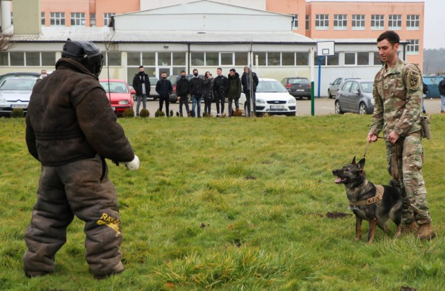 U.S. Army Cpl. Dustin Borchardt, a military working dog handler with the 100th Military Police Detachment based out of Stuttgart, Germany, demonstrates his dog's obedience during a bite suit demonstration in Ferizaj/Ferizaje, Kosovo, on Dec. 8, 2020. Borchardt and his dog Pearl travelled to the School of Agribusiness and Food Technology to share knowledge about working dogs and build a relationship with the local community.