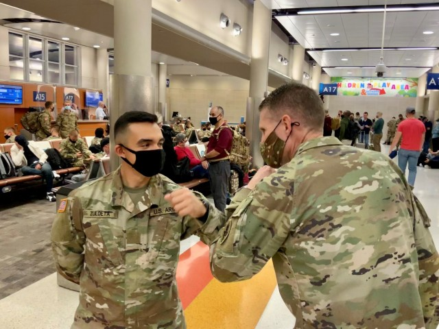 Pvt. Luis Zuloeta, a 68W Combat Medic who just graduated from the U.S. Army Medical Center of Excellence (MEDCoE) is greeted by CSM Clark Charpentier with a COVID appropriate elbow bump as he awaits travel home to New Jersey for Holiday Block Leave at the San Antonio International Airport on December 19, 2020.