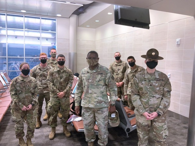 Drill Sergeant Jeffrey Markham (far right) and Chaplain (Maj.) Oyedeji Idowu (center) speak with Soldiers in training at the U.S. Army Medical Center of Excellence as they await flights from the San Antonio International Airport for Holiday Block Leave on December 19, 2020.
