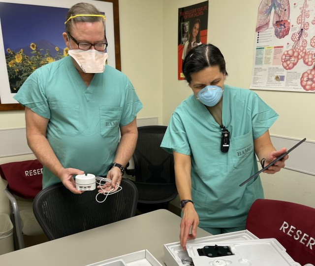 Mike Lavers, sleep technician, and Sgt. 1st Class Annabelyn Verdeflor, noncommissioned officer in charge of the Pulmonary Clinic, look over the components of a home healthcare kit as part of the COIVD-19 Remote Monitoring Program, a joint effort of the Virtual Medical Center and Brooke Army Medical Center, Joint Base San Antonio-Fort Sam Houston, Texas, Dec. 18, 2020. The program equips COVID-19 patients needing additional monitoring with a home kit and 24/7 oversight to ensure a higher level of post-hospital care.