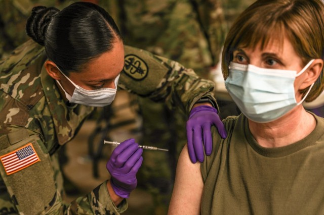 Staff Sgt. Brenda Collins, medical specialist, from Carl R. Darnall Army Medical Center administers the COVID-19 vaccination to a patient during the phase one process Dec.15, 2020 at on Fort Hood, Texas. Distribution of the vaccine will be conducted in phases based on CDC guidance. The vaccine is stored and distributed under various controls to ensure the safety of the recipient.