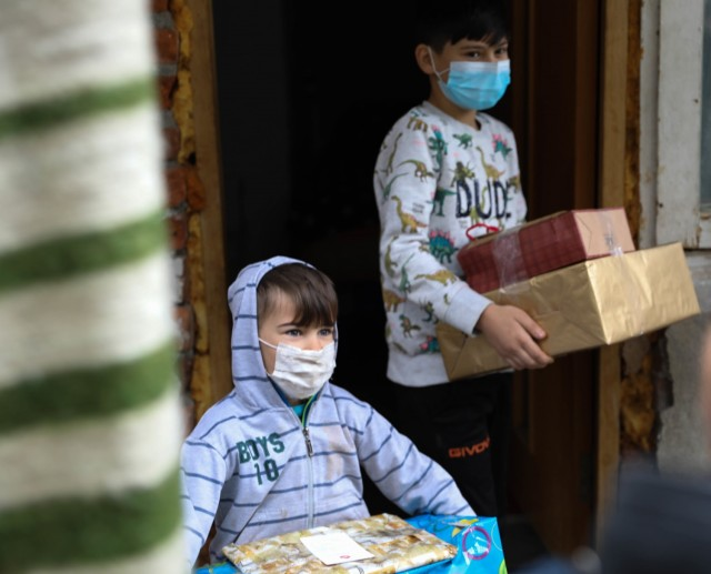 BUCHAREST, Romania – Two brothers walk outside with the Christmas presents they just received on Dec. 21. Through the combined efforts of Civil Affairs Team 3231, 432nd Civil Affairs Battalion, Green Bay, Wis., Office of Defense Cooperation, U.S. Embassy, 3rd Battalion, 15th Infantry Regiment, Army Support Activity-Black Sea, Area Support Group-Black Sea Staff, and other Service Members at Mihail Kogalniceanu Air Base, not only did 125 children receive clothing and toys, the Salvation Army was able to surpass their overall goal and reached 300 kids with Project Angel Tree this holiday season. (U.S. Army Photo by Sgt. H. Marcus McGill)