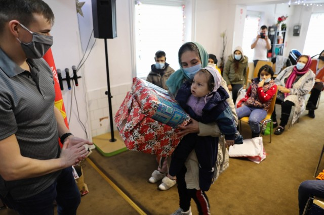 BUCHAREST, Romania – Sgt. Garrett Montalvo, Civil Affairs Sgt., Civil Affairs Team 3231, 432nd Civil Affairs Battalion, Green Bay, Wis., hands Christmas presents to a small child and her grandmother here on Dec. 21. Through the combined efforts of Civil Affairs Team 3231, Office of Defense Cooperation, U.S. Embassy, 3rd Battalion, 15th Infantry Regiment, Army Support Activity-Black Sea, Area Support Group-Black Sea Staff, and other Service Members at Mihail Kogalniceanu Air Base, not only did 125 children receive clothing and toys, the Salvation Army was able to surpass their overall goal and reached 300 kids with Project Angel Tree this holiday season. (U.S. Army Photo by Sgt. H. Marcus McGill)