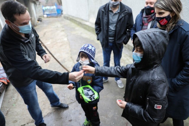 BUCHAREST, Romania – Roxy Sandu, Regional Leader, Salvation Army, Romania looks on as Capt. Greg Caruso Team Chief, Civil Affairs Team 3231, 432nd Civil Affairs Battalion, Green Bay, Wis., gives two brothers U.S. Army rank patches and U.S. and Romanian partnership stickers on Dec. 21. Through the combined efforts of Civil Affairs Team 3231, Office of Defense Cooperation, U.S. Embassy, 3rd Battalion, 15th Infantry Regiment, Army Support Activity-Black Sea, Area Support Group-Black Sea Staff, and other Service Members at Mihail Kogalniceanu Air Base, not only did 125 children receive clothing and toys, the Salvation Army was able to surpass their overall goal and reached 300 kids with Project Angel Tree this holiday season. (U.S. Army Photo by Sgt. H. Marcus McGill)