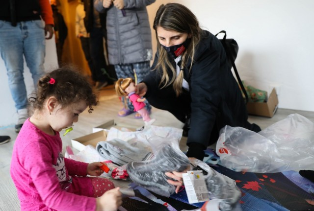 BUCHAREST, Romania – Roxana Sandu, Regional Leader, Salvation Army, Romania goes through presents with a young girl in her living room here on Dec. 21. Through the combined efforts of Civil Affairs Team 3231, 432nd Civil Affairs Battalion, Green Bay, Wis., Office of Defense Cooperation, U.S. Embassy, 3rd Battalion, 15th Infantry Regiment, Army Support Activity-Black Sea, Area Support Group-Black Sea Staff, and other Service Members at Mihail Kogalniceanu Air Base, not only did 125 children receive clothing and toys, the Salvation Army was able to surpass their overall goal and reached 300 kids with Project Angel Tree this holiday season. (U.S. Army Photo by Sgt. H. Marcus McGill)