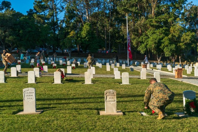 Service members adorning graves with holiday wreaths at the Presidio of Monterey cemetery during the fourth annual Wreaths Across America event on Saturday, December 19.