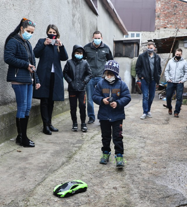 BUCHAREST, Romania – Roxana Sandu, Regional Leader, Salvation Army, Romania and members of Civil Affairs Team 3231, 432nd Civil Affairs Battalion, Green Bay, Wis., look on with a boy and his mother as the younger brother plays with his new remote control car here on Dec. 21. Through the combined efforts of Civil Affairs Team 3231, Office of Defense Cooperation, U.S. Embassy, 3rd Battalion, 15th Infantry Regiment, Army Support Activity-Black Sea, Area Support Group-Black Sea Staff, and other Service Members at Mihail Kogalniceanu Air Base, not only did 125 children receive clothing and toys, the Salvation Army was able to surpass their overall goal and reached 300 kids with Project Angel Tree this holiday season. (U.S. Army Photo by Sgt. H. Marcus McGill)