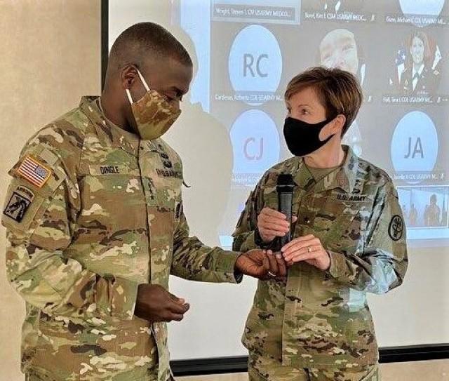 Regional Health Command-Atlantic Commanding General Brig. Gen. Paula Lodi presents Lt. Gen. R. Scott Dingle, Army Surgeon General and U.S. Medical Command Commanding General, with a regional coin during the region's strategic leadership forum.