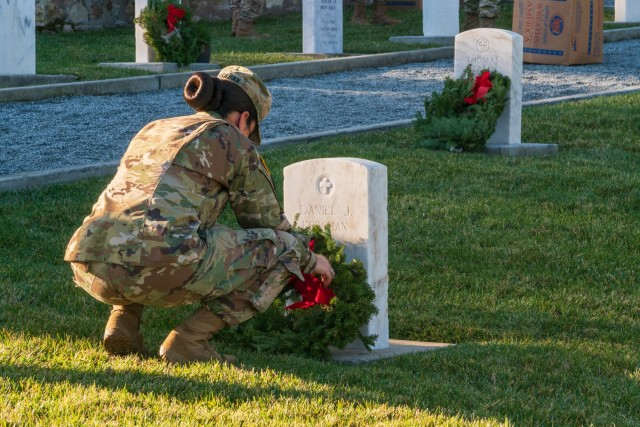 A Soldier adorning a grave with a holiday wreath at the Presidio of Monterey cemetery during the fourth annual Wreaths Across America event on Saturday, December 19.