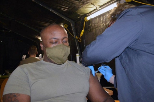 U.S. Army Staff Sgt. Jamaal Cromer, an Army medic assigned to U.S. Army Health Clinic Ansbach, receives the Moderna COVID-19 vaccine from Nurse Claudia Aikens at USAHC Ansbach Clinic, Ansbach, Germany, Dec. 28, 2020. Cromer is the first to receive the COVID-19 vaccine in the Ansbach military community.
