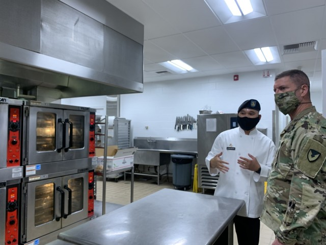 Staff Sgt. Cabansag briefs Maj. Gen. Daniel Mitchell, commanding general of the Army Sustainment Command on the updated equipment in the kitchen and the increased capability that the equipment provides for his cooks.