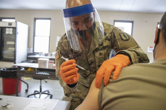 U.S. Army Staff Sgt. Nigel Chen, assigned to Joint Task Force COVID-19, New York National Guard, administers the Pfizer-BioNTech COVID-19 vaccine at the Camp Smith Training Site Medical Readiness Clinic, N.Y., on December 18, 2020. The New York National Guard is participating in a Department of Defense vaccine pilot program in which 44,000 doses of the Pfizer vaccine are being administered to front line medical personnel at 16 locations around the world.