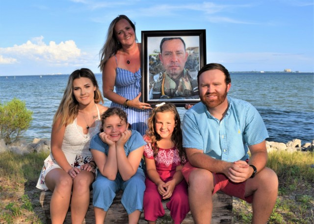 Sarah Smith holds a framed photograph of her late husband, Sgt. 1st Class James Smith during a beachfront family photo this year. Smith took part in the 94th Training Force Sustainment Headquarters and Headquarters Company virtual suicide prevention training, where she shared her story about the loss of her husband due to suicide. The 94th TD-FS HHC suicide prevention training was conducted on Oct. 24, 2020.If you or someone you know is in crisis, contact the National Suicide Prevention Lifeline at (800) 273-8255 or Military Crisis Line, free support for all Service members, including members of the National Guard and Reserve, and all Veterans at (800) 273-8255.