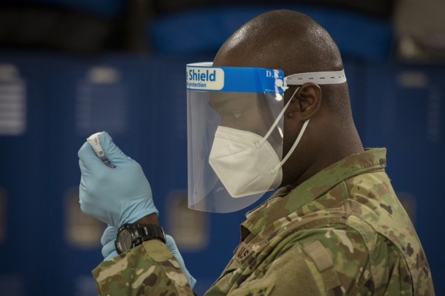 Army Staff Sgt. Donnell Niles draws the Moderna COVID-19 vaccine from a vial into a syringe at Bradley Air National Guard Base in East Granby, Conn., Jan. 2, 2021.