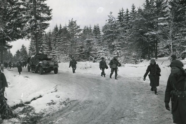 Soldiers with the Army's 17th Airborne Division walk ahead of a military vehicle on a snow-covered road near Houffalize, Belgium, in January 1945.