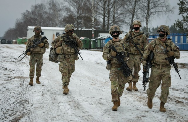 Troopers assigned to 2nd Battalion, 8th Cavalry Regiment, 1st Armored Brigade Combat Team, 1st Cavalry Division, march down the Pabrade Training Area, Lithuania, range road as they support a live fire demonstration Dec. 22, 2020.