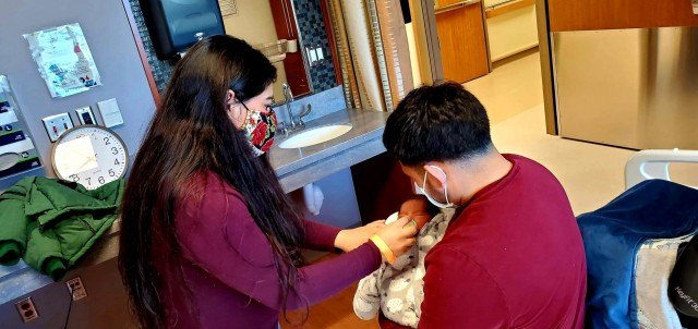 Sgt. Alan Delcid and Quetzali Gisselle Delcid Juarez tend to baby Landon, the first baby born at BMACH in 2021.