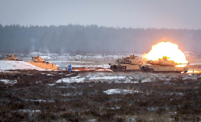 Bradley Fighting Vehicles are bathed in a red and orange glow from ignited gasses as an M1 Abrams tank's main gun fires Dec. 22, 2020, at the Pabrade Training Area, Lithuania. The vehicles, assigned to 2nd Battalion, 8th Cavalry Regiment, 1st Armored Brigade Combat Team, 1st Cavalry Division, conducted firing maneuvers as part of a live fire demonstration that showcased the battalion's battlefield lethality.