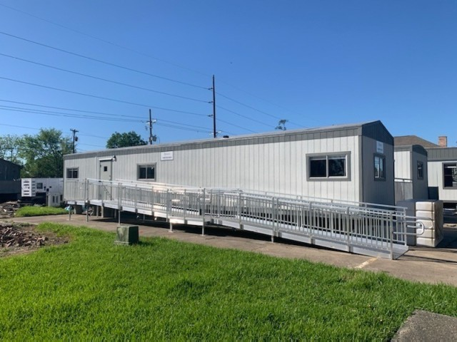 These trailers were set up at a vaccine trial location in Lake Charles, Louisiana.  The ramps were installed to assure compliance with the Americans with Disabilities Act.  This photo was taken before Hurricane Delta struck the Lake Charles area; the trailers made it through the storm with minimal damage.  (Photo by Sgt. 1st Class Joseph Love, LOGCAP Support Brigade)