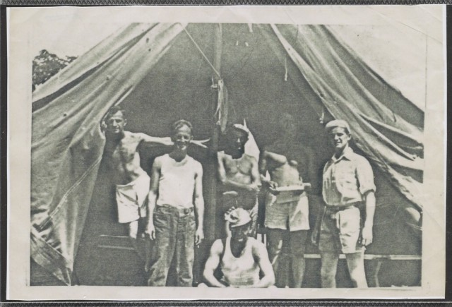 Dan Crowley, on the far right, stands inside a tent with other service members in the Philippines during World War II.