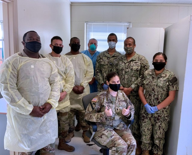 Lt. Col. Nadia M Pearson, MEDCoE Command Surgeon (seated) poses for a group photo with members of the Holiday Block Leave Team Reintegration Testing Cell.