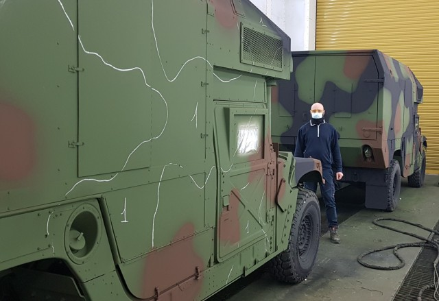 Alessio Maenza, a painter from the Directorate of Maintenance, Army Field Support Battalion – Africa, 405th Army Field Support Brigade, stands next to one of the dozens of military vehicles he re-painted. The vehicles are part of Army Prepositioned Stock-2 and a key element in support of U.S. Army Europe and Africa's power projection and warfighter readiness.