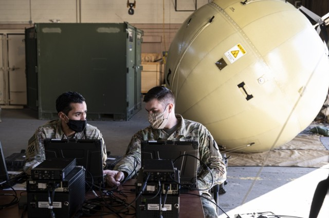 Chief Warrant Officer 2 Nathan Paquette and Chief Warrant Officer 2 Carlos Gil, network management technicians, 4th Space Company, 1st Space Battalion, test a Ground Antenna Transmit and Receive satellite communication terminal at Fort Carson, Colorado, Dec. 9, 2020. GATRs are inflatable, easily deployable antennas that enable high-bandwidth satellite communications. The 1st Space Battalion is assigned to the 1st Space Brigade, U.S. Army Space and Missile Defense Command. (U.S. Army photo by 1st. Sgt Steve Segin/RELEASED)