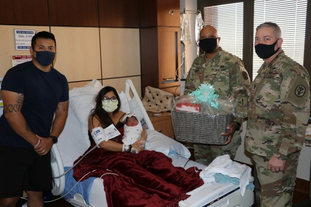 Brig. Gen. Shan Bagby, commander, Brooke Army Medical Center, and Command Sgt. Maj. Thurman Reynolds deliver a gift basket to U.S. Air Force Staff Sgt. Jessica Ojeda-Nolasco, a C5 aviation research manager at Lackland Air Force Base, husband Isaac Nolasco and their daughter Stella Luna at BAMC, Jan. 2, 2021. Stella Luna was the first baby born at BAMC, Jan. 1, 2021, at 3:26 a.m., weighing 8 pounds, and 2 ounces. (U.S. Army photo by Robert A. Whetstone)