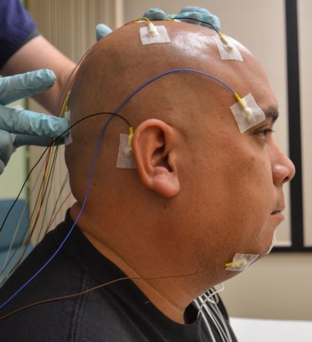 U.S. Army Sgt. 1st Class Bobby M. Scharton, a platoon sergeant with 17th Fires Brigade, 7th Infantry Division, remains still as Christopher Taylor, a sleep technician with Madigan Army Medical Center, applies a sensor during a sleep study at Joint Base Lewis-McChord, Wash., Nov. 22, 2013. Physicians use data from the studies to diagnose severe sleep disorders like sleep apnea and insomnia.